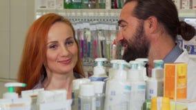Knappe gebaarde apotheker die zijn vrouwelijk klant gevraagd product geven stock footage