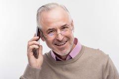 Knappe gebaarde hogere mens die gelukkig terwijl het hebben van telefoongesprek voelen royalty-vrije stock foto's