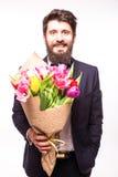 Knappe gebaarde mens die in kostuum, met baard en aardig boeket van bloemen dragen Stock Foto
