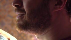 Knappe gebaarde mens die wat parfum op zijn hals bespuiten Langzaam motieschot, de mening van het profielclose-up stock footage