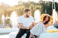 Knappe gebaarde mens en zijn mooi meisje die dichtbij fonteinen rusten royalty-vrije stock foto