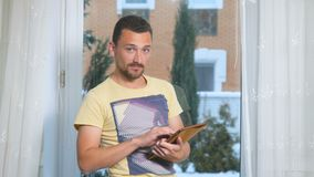 Knappe gebaarde mens met tablet voor venster stock video