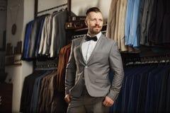 Knappe gebaarde zakenman in klassiek kostuum Een jonge modieuze mens in een doekjasje Het is in de toonzaal, die op kleren, pos p Royalty-vrije Stock Fotografie