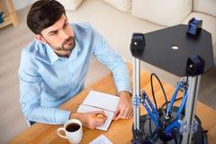 Knappe geconcentreerde mens die 3d printer met behulp van Stock Foto