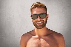 Knappe gelooide mens met in kapsel, varkenshaar, topless status, aantonend zijn spierlichaam, die zonnebril dragen, die ple hebbe royalty-vrije stock afbeeldingen