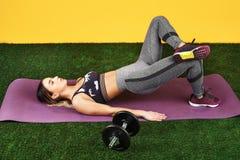 Knappe geschikte jonge woman do exercise met domoren op de geschiktheids purpere mat op groen gras over gele achtergrond stock afbeeldingen