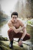 Knappe geschikte shirtless jonge mens naast watervijver of rivier Stock Afbeelding