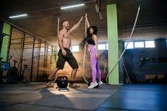 Knappe geschikte vrouw en man die elkaar hoogte vijf na harde succesvolle opleiding in de gymnastiek geven royalty-vrije stock afbeeldingen