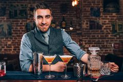Knappe glimlachende barman die van het werk genieten en cocktails voorbereiden bij bar Stock Afbeeldingen