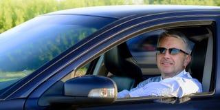 Knappe glimlachende bedrijfsmens in een auto Stock Afbeelding