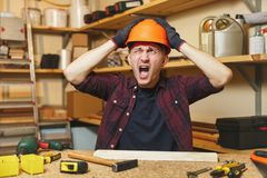 Knappe glimlachende jonge mens die in timmerwerkworkshop op houten lijstplaats werken met stuk van hout stock afbeelding