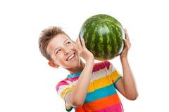 Knappe glimlachende kindjongen die groen watermeloenfruit houden Royalty-vrije Stock Afbeeldingen