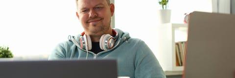 Knappe glimlachende mannelijke student die online gebruiken stock foto's