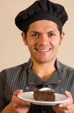 Knappe glimlachende mens die een stuk van donkere chocoladecake houden op een zachte bruine achtergrond Royalty-vrije Stock Fotografie