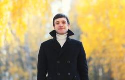 Knappe glimlachende mens die een zwart laagjasje in de herfstdag dragen royalty-vrije stock afbeelding