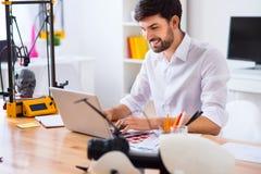 Knappe glimlachende mens die laptop met behulp van Stock Afbeelding