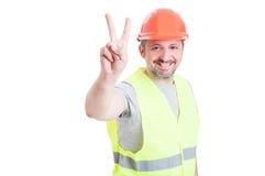 Knappe glimlachende werkman of aannemer met helm die vict tonen royalty-vrije stock afbeelding