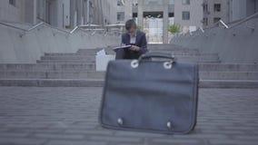 Knappe goed-geklede jongenszitting op de treden op de straat die het huiswerk doen bij de achtergrond Oude beurs die zich bevinde stock videobeelden