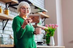 Knappe grootmoeder het feesten ogen met familiebeeld in kader stock afbeeldingen