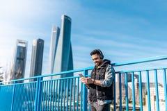 Knappe Hipster Guy Listening Music op Hoofdtelefoons en het Gebruiken van Cellphone stock foto's