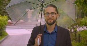 Knappe hipsterzakenman onder de parapluglimlachen positief in camera in park stock video