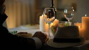Knappe hogere man die in kostuum op vrouw in restaurant, romantische datum wachten stock footage