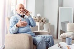 Knappe hogere mens die op de telefoon met zijn vriend spreken royalty-vrije stock foto