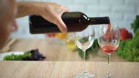 Knappe hogere mens die rode wijn in glazen gieten, drank het proeven, viering stock video