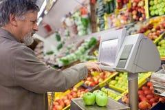 Knappe hogere mens die voor vers fruit winkelt Royalty-vrije Stock Foto