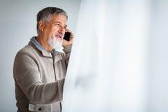Knappe hogere mens die zijn celtelefoon uitnodigen stock foto