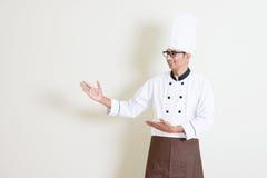 Knappe Indische mannelijke chef-kok in eenvormig tonend iets Royalty-vrije Stock Foto