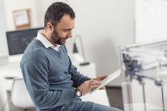 Knappe ingenieur die aan tablet in bureau werken Royalty-vrije Stock Foto's
