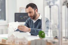 Knappe ingenieur die 3D model van huis controleren Stock Afbeelding