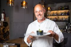 Knappe Italiaanse mens kaal met een baard in witte eenvormige chef-kok in een restaurant die met een toothy glimlach in zijn hand stock afbeelding