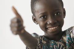 Knappe jonge Afrikaanse jongen die zijn duimen tonen als succes sy stock afbeelding