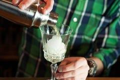 Knappe jonge barman in groen overhemd die en zich dichtbij houten teller in bar bevinden werken stock afbeelding