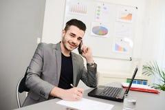 Knappe jonge bedrijfsmens die in bureau met toevallige cothes werken Royalty-vrije Stock Afbeelding