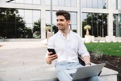 Knappe jonge bedrijfsmensenzitting die in openlucht laptop computer en mobiele telefoon met behulp van stock foto
