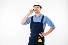 Knappe jonge bouwer in het algemene spreken op mobiele telefoon Stock Foto