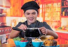 Knappe jonge cheff die een gastronomisch Zwitsers fonduediner met geassorteerde kazen en een verwarmde pot van kaasfondue voorber stock afbeelding