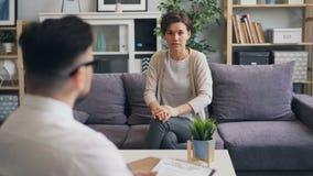 Knappe jonge dame die gevoel en emoties met psychlogist in bureau delen stock video