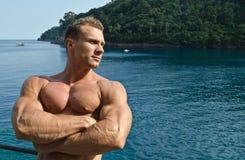 Knappe jonge die bodybuilder, wapens met erachter overzees worden gekruist, grote copyspace Stock Foto's