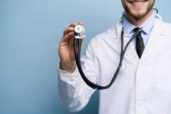 Knappe jonge dokter die die een stethoscoop houden, over lichtblauw wordt geïsoleerd stock afbeeldingen