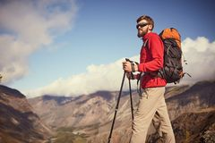 Knappe jonge gebaarde mannelijke wandelaar die zich op de rand van een canion bevinden die weg eruit zien Stock Foto's