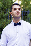 Knappe jonge gebaarde mens met wit overhemd en vlinderdas op de straat Stock Foto