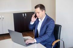 Knappe jonge geconcentreerde aantrekkelijke mens die cellphone gebruikt terwijl het werken met laptop in het bureau royalty-vrije stock fotografie