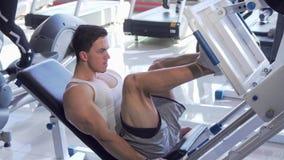 Knappe jonge gescheurde mannelijke atleet die op de machine van de beenpers uitoefenen stock footage