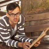 Knappe jonge het boek in openlucht dichte omhooggaand van de mensenlezing Stock Fotografie