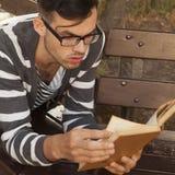 Knappe jonge het boek in openlucht dichte omhooggaand van de mensenlezing Royalty-vrije Stock Foto's