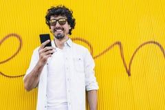 Knappe jonge hipstermens met mobiele telefoon stock afbeelding